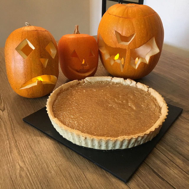 A whole Pumpkin Pie in front of carved pumpkins