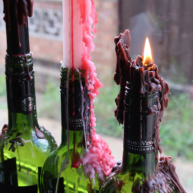 The three varieties of dripping taper candle in wine bottles, lit and quite melted