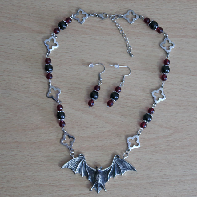 A stainless steel necklace with a bat centrepiece, red glass beads and gothic-style elements