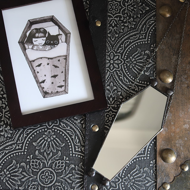 A Print by Marcies Art and a coffin-shaped mirror by August Glass Designs