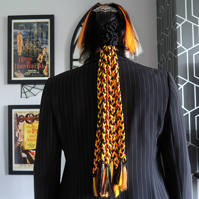 Long black, orange and yellow plaits, with orange and white weft clip-in hair