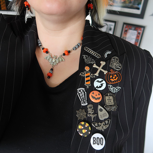 Close up of bat necklace and Halloween-themed pins